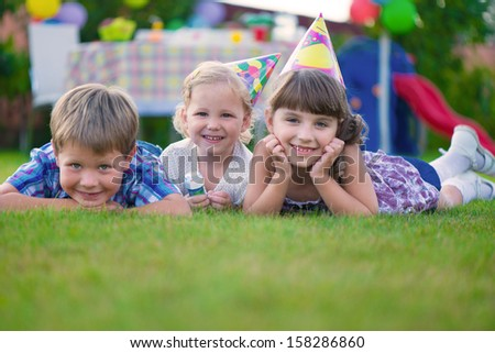 Three little kids celebrating birthday on green grass - stock photo