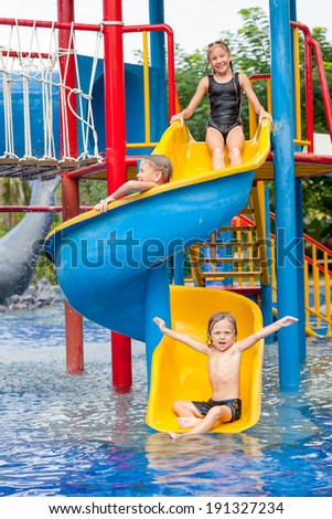 Stock photo three little kids playing in the swimming pool on the