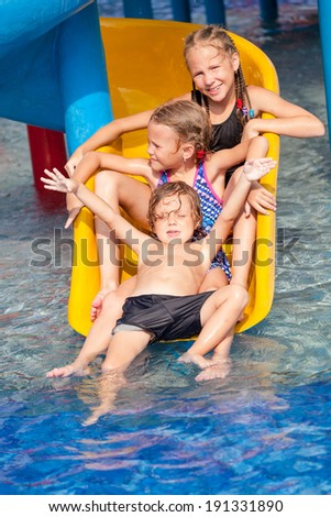 three little kids playing in the swimming pool on the slide - stock photo
