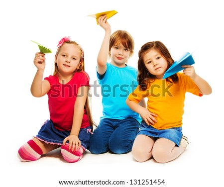 Three little kids sitting with colorful paper plane, boy and girl, Caucasian and Asian, isolated on white