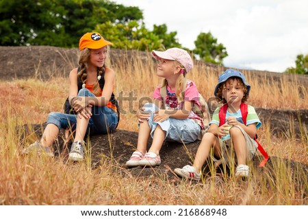 three little kids with backpack sitting on the footpath in the mountains at the day time - stock photo