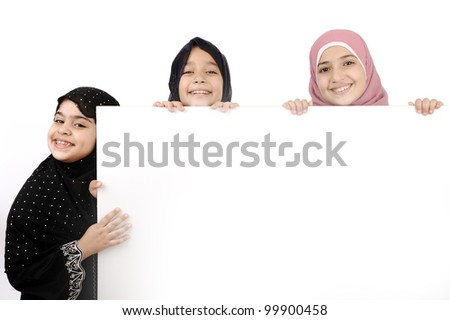 Three little schoolgirls holding a blank white sign for your message. Good for borders of articles or websites. Beautiful arabic muslim models. Isolated on white background.