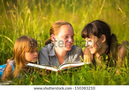 Three little sister reading book in natural environment together - stock photo