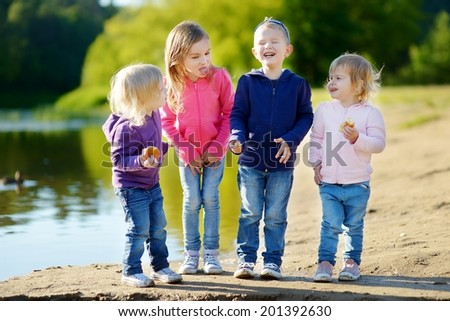 Three little sisters and their brother eating buns, laughing and joking by a river at sunny autumn day - stock photo