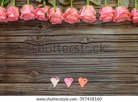 Three little Valentines Day paper heart objects and neatly arranged row of pink roses - stock photo