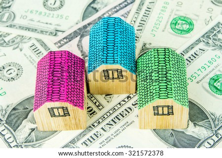 three little wooden houses are laying on one dollar banknotes - stock photo