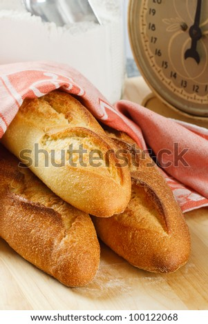 Three loaves of fresh baked baguette bread with flour and scale in the background