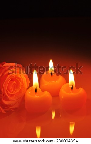 three luminous pink candlehearts with pink rose in red light - stock photo