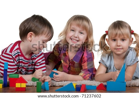 Three lying on the carpet children are playing blocks; isolated on the white background - stock photo