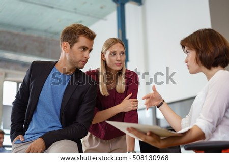 Three male and female people gesturing while meeting about something in small office