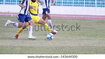 Three male soccer players competing for the ball, close up view.