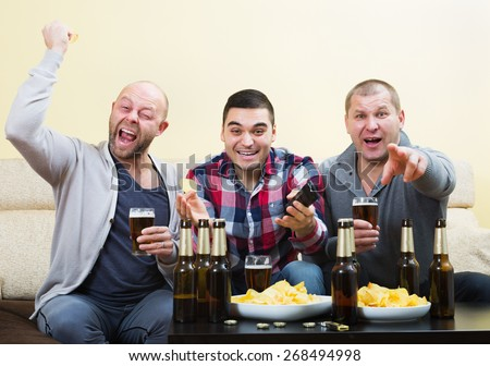 Three male sport fans watching hockey game heatedly in livingroom - stock photo