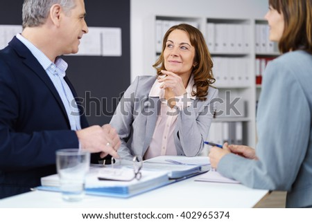 Three managerial business colleagues in a meeting sitting grouped around a table having a serious discussion, focus to an attractive middle-aged woman - stock photo