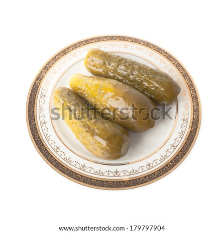 Three marinated cucumbers on the plate isolated over white