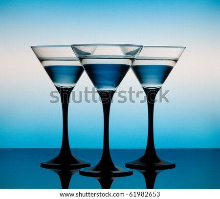 Three martini glass on a blue background - stock photo