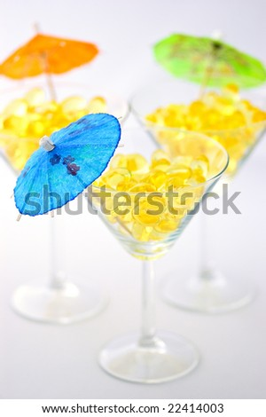 Three martini glasses filled with cod liver oil capsules, sources of vitamin a, vitamin d and omega-3, decorated with mini parasols, over white background