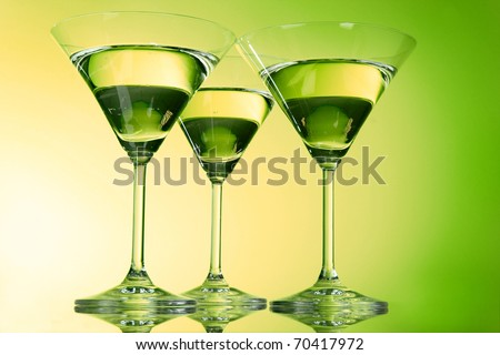 Three martini glasses on green background - stock photo