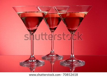 Three martini glasses on red background - stock photo