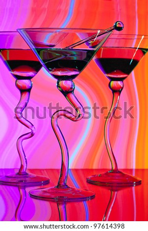 Three martinis in glasses with curved stems in front of colorful lighted background showing shades of yellow, pink, blue, red and orange. - stock photo