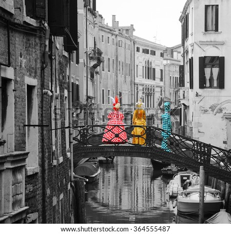Three masks in checkered colorful costumes standing on the bridge over canal. Back view. Carnival in Venice (Italy). Toned black and white photo.