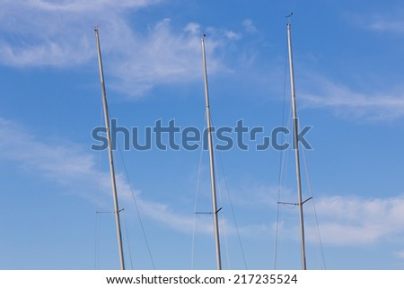 Three masts against a blue sky. - stock photo