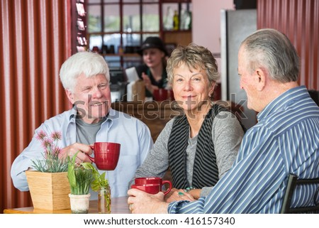 Three mature friends in a coffee house - stock photo