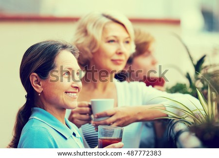 Three mature women drinking tea with cookies at balcony. Focus on brunette
