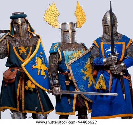 Three medieval knights isolated on grey background. - stock photo