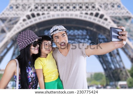 Three member of asian tourist take self portrait together in eiffel tower - stock photo