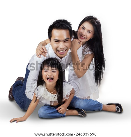Three member of happy family playing together in the studio while laughing happily - stock photo