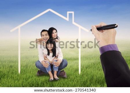 Three member of happy family smiling at the camera under a dream house on the meadow - stock photo