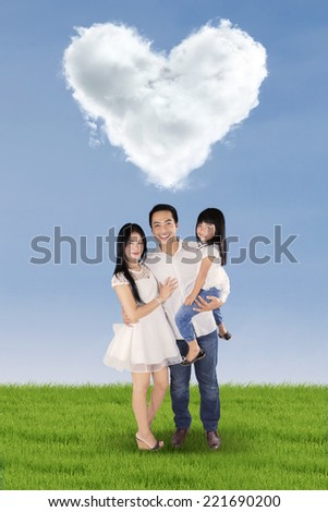 Three member of happy little family standing on the meadow under cloud shaped heart
