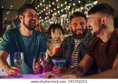 Three men are talking and laughing while enjoying drinks in a night club.