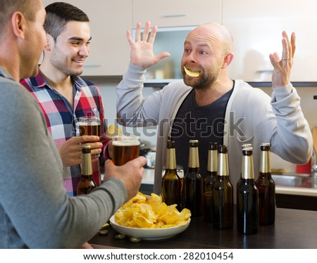 Three men drinking beer and laughing at house party - stock photo