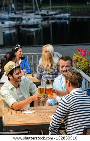Three men drinking beer at terrace bar enjoying night out - stock photo