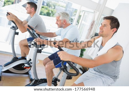 Three men exercising on fitness bikes at gym - stock photo