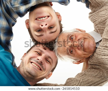 Three men generations looking down into camera - stock photo