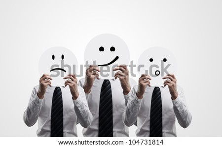 three men hold plates with smilies on white background - stock photo