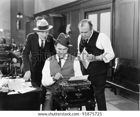 Three men in an office hunched over a typewriter