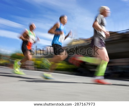 Three men in blurred motion in running competition