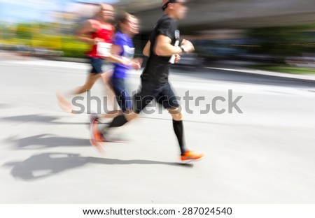 Three men in blurred motion in running competition on bright sunny summer day - stock photo