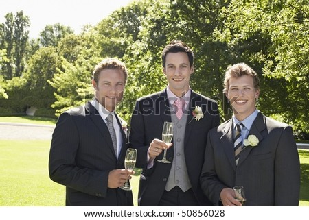 Three men in garden, wearing full suits, holding wineglasses, portrait