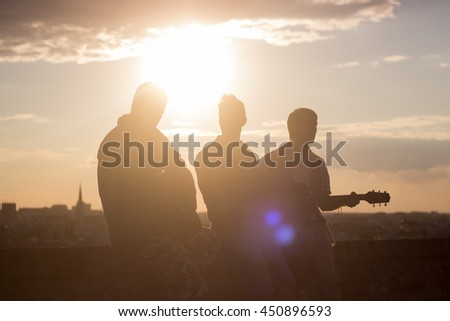 Three men music band backlit guitar. Strong lens flare sunlight sun. Warm colors yellow orange