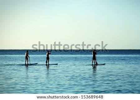 Three men paddle-boarding at Caribbean Sea - stock photo