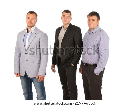 Three men posing for the camera standing in a row at an angle, one in a jacket, one a suit and the last his shirtsleeves, isolated on white - stock photo