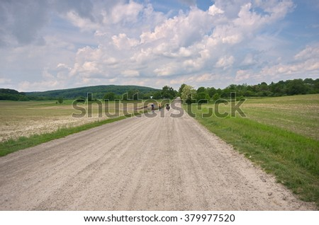Three men riding bicycles along country roads. Gravel path in summer landscape with sunny day and hills covered with forests in background. Clouds are gathering in the sky. Soon there will be a storm. - stock photo