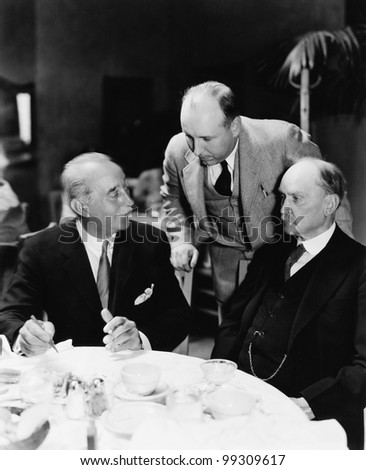 Three men sitting together at a table