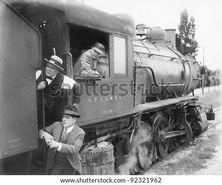 Three men waiting at  a steam locomotive - stock photo