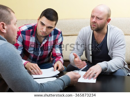 Three men with documents discussing