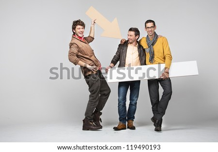 Three men with empty board and arrow